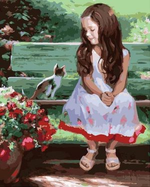 Girl smiling at kitten on bench